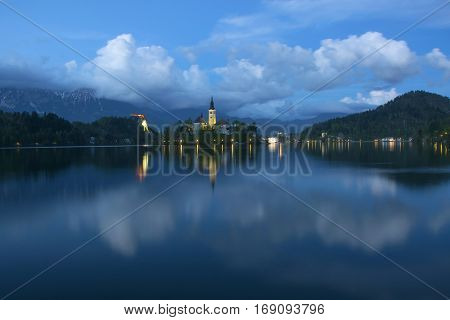 Island on Bled lake and pilgrimage church of the Assumption of Mary reflected in water with moving clouds on background at twilight, Slovenia