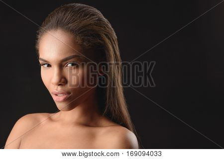 Seductive young nude mulatto girl is standing and looking at camera with desire. Isolated and copy space in right side