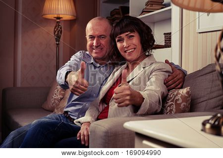 A mid short of two cute people showing their thumbs-up, demonstrating harmony and happiness, loving each other. Individuals wearing mainly classic clothes