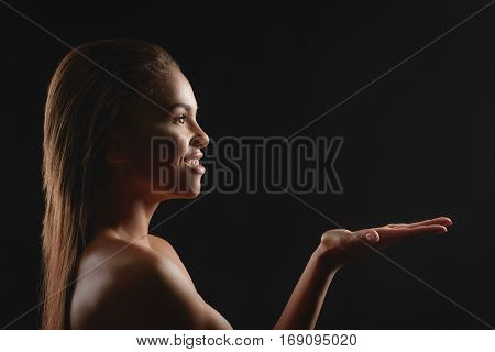 Cheerful naked mulatto woman is showing something and smiling. She is raising hand up for presentation. Isolated on black background