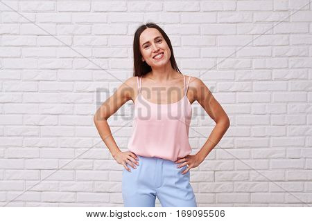 Wearing pastel silk top and trousers posing over white background. Positive genuine smile of happy woman. Wearing stylish clothes