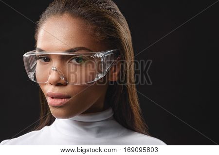 Pretty mulatto girl in modern glasses in looking forward with serenity. Isolated and copy space in right side