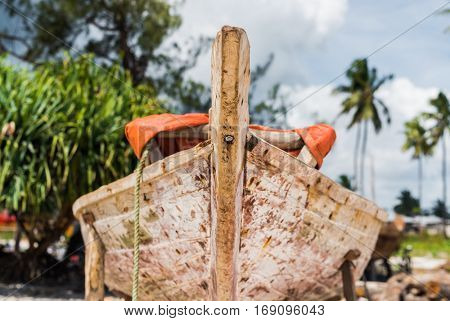 african wooden fishing boat stern with palms and sky on the background