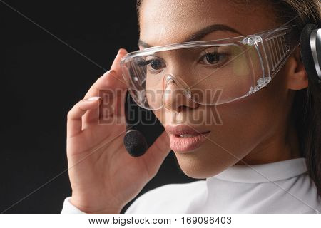 Pensive young mulatto operator is speaking into microphone. She is wearing contemporary eyeglasses. Isolated on black background