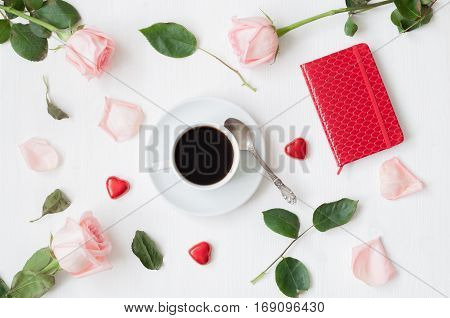 Romantic love still life - cup of coffee peach roses red notebook owl shaped clock heart shaped candies on white background. Love romantic background