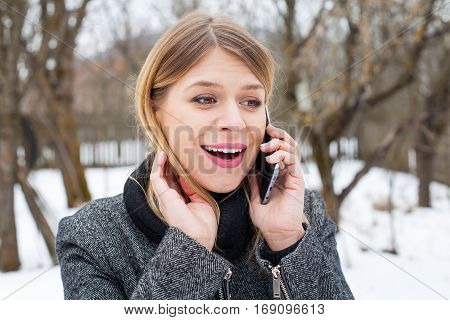 Picture of a surprised young woman on the phone - outdoor winter