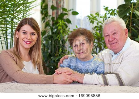 Picture of an elderly couple with their happy caregiver at home