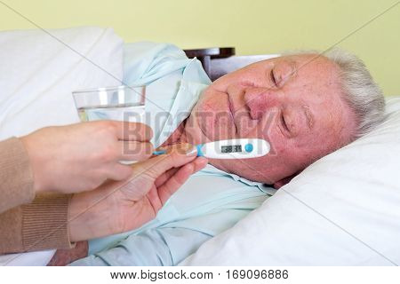 Picture of a sick old man in bed having fever
