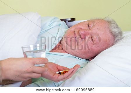Picture of a sick old man in bed his caregiver giving him medicine
