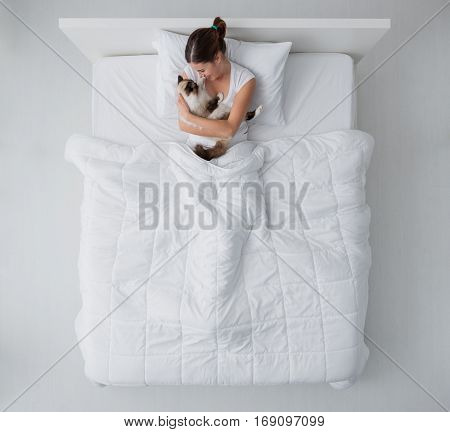 Young woman lying in bed and holding her beautiful birman cat top view