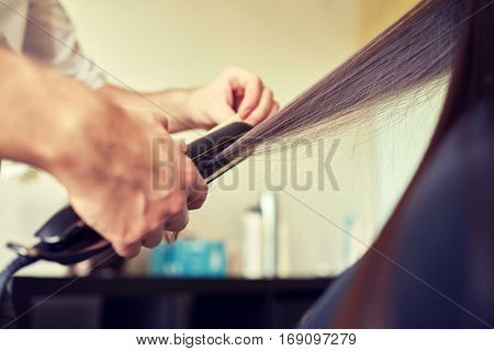 beauty, hairstyle, hot styling and people concept -  close up of stylist hands with styling iron straightening woman hair at salon