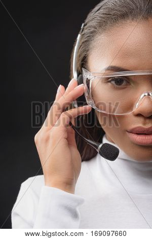 Close up of half of female face. Skillful call center assistant is speaking into microphone with serenity. Isolated
