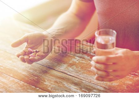 healthy lifestyle, medicine, nutritional supplements and people concept - close up of male hands holding pills with cod liver oil capsules and water glass
