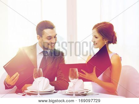 restaurant, couple and holiday concept - smiling man looking into girlfriends or wifes menu at restaurant