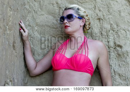 portrait of the bright woman in a bathing suit at a wall a subject beautiful women