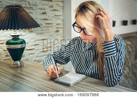 girl sitting at the table and writes in a paper notebook amounts to a list write poetry write down their thoughts and thinking