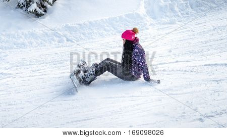 girl snowboarder fell and sitting on the snow in the winter