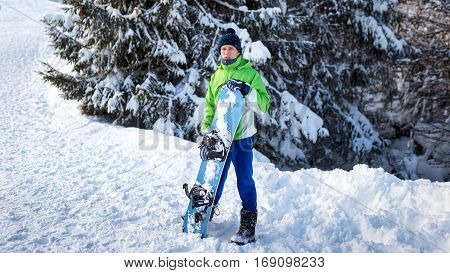 snowboarder standing on the snow and keeps the board in his hands