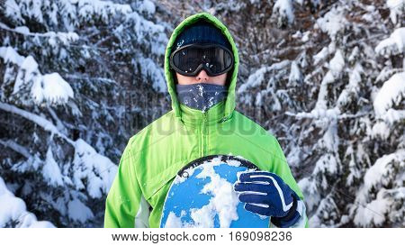 snowboarder standing among the snow-capped fir trees in a ski mask and holding a board by hand close-up portrait