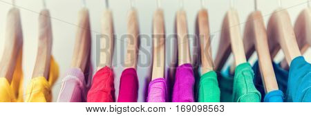 Banner horizontal crop for text background of clothing rack. Clothes for women hanging on hangers in home closet or shopping mall for store sale concept. Colorful selection of t-shirts.