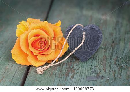 Orange rose and a heart from slate on an old shabby wooden table for a mothers day card
