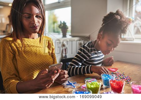 Woman Checking Phone While Child Does Beading