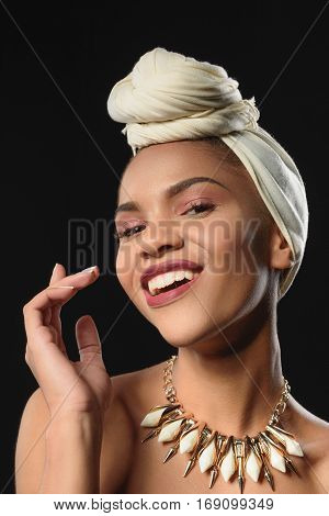 Happy young mulatto woman is standing and laughing. She is wearing traditional scarf on head and jewelry on neck. Isolated