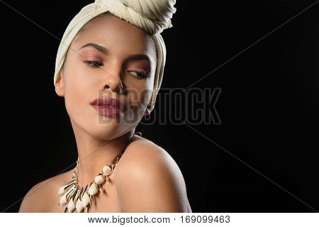 Waist up portrait of passionate young african girl posing in traditional headscarf and necklace. Isolated and copy space in right side