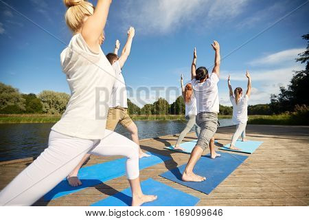 fitness, sport, yoga and healthy lifestyle concept - group of people making high lunge or crescent pose on river berth