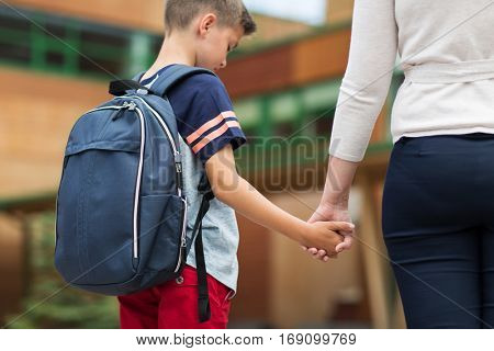 education, childhood, family and people concept - sad elementary student boy with mother at school yard