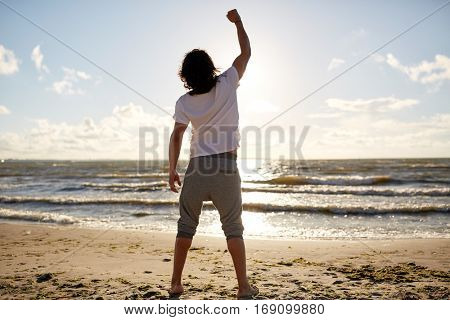 people, success, achievement and power concept - man with rised fist on beach