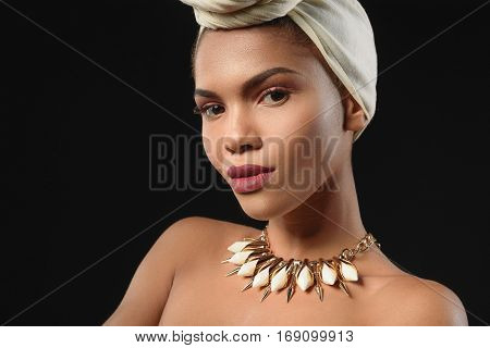 I respect african culture. Confident young girl is standing in turban and necklace. She is looking at camera with seriousness. Isolated on black background