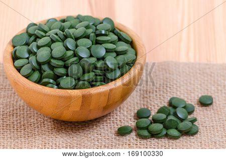 green pills spirulina and chlorella seaweed close up n the wooden bowl