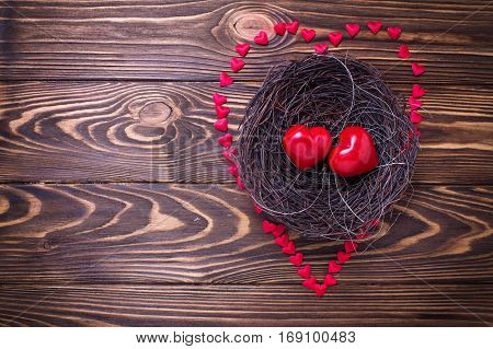 Little hearts in nest on wooden background. Flat lay.Top view. St. Valentine day background. Place for text.
