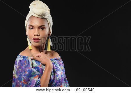 Voluptuous young mulatto girl is wearing cultural headscarf and colored earrings. She is looking at camera with desire. Isolated and copy space in right side