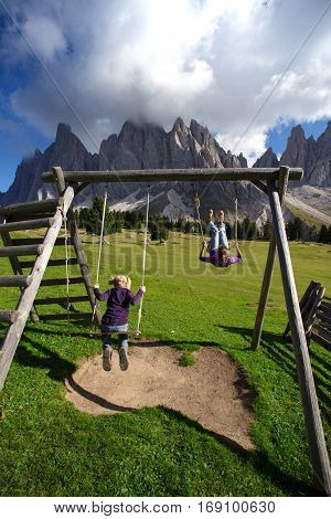 Girls sister swinging on a swing in the park Puez Odle. Italy