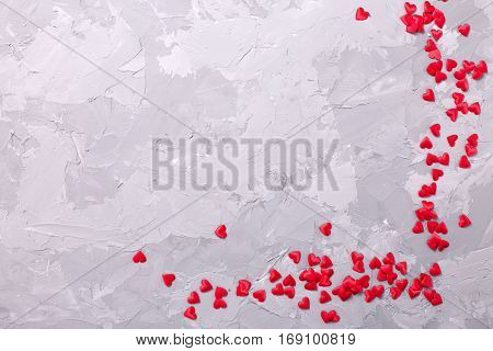 Many little decorative red hearts on textured grey background. Flat lay with copy space. St. Valentine day background.