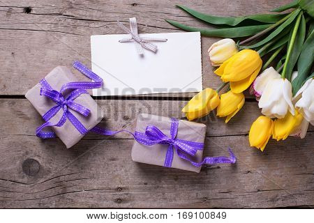 Yellow and white spring tulips empty tag and wrapped boxes on vintage wooden background. Selective focus. Place for text.
