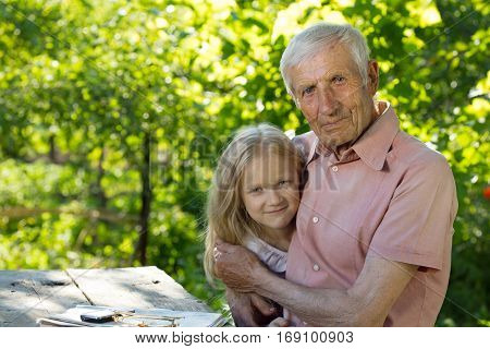 portrait of senior man and the great-granddaughter sitting at a table in the garden