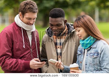 people, friendship, communication, technology and international concept - group of happy friends with smartphone and coffee outdoors