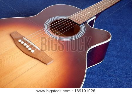 Classic acoustic six strings guitar sunburst color top from spruce with cutaway fragment on jeans background side view closeup