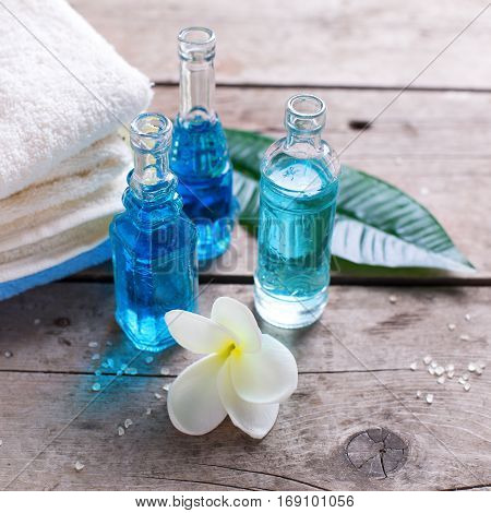 Bottles with aroma oil tropical flowers plumeria and towels on wooden background. Selective focus. Place for text. Square image.