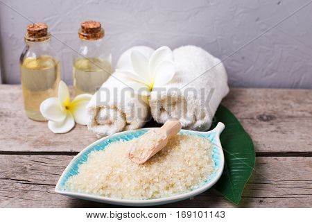 Spa setting. Sea salt in bowl in form of leaf bottles with aroma oil and towels on vintage wooden background. Selective focus is on salt.