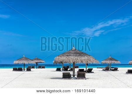 Sandy tropical beach with deckchairs and sunshades on a small island resort in Maldives, Indian Ocean. Holidays destination
