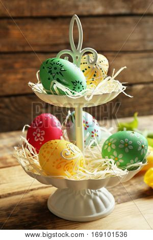 Tier stand with beautiful Easter eggs on wooden background, closeup
