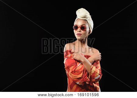 Combination of modern fashion and african tradition. Shy young girl is standing in headscarf, sunglasses and colorful blouse. Isolated and copy space in left side