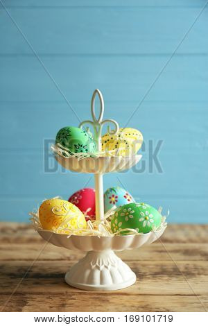 Tier stand with beautiful Easter eggs on blue wooden background