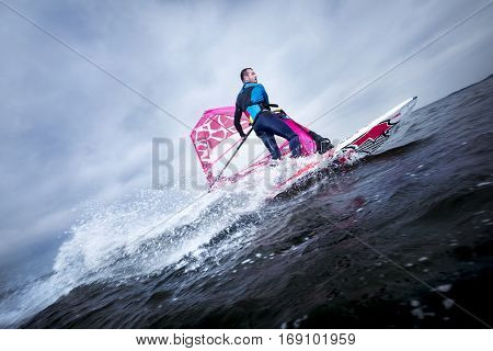 A windsurfer tilts the rig and carves the board to perform a planing or jibe