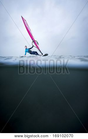 frontview windsurfer in an over underwater shot