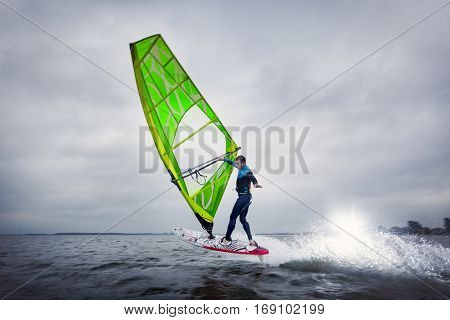 professional windsurfer jumps and does a onehanded trick
